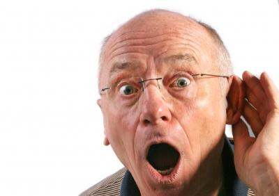 Ein Senior hält seine Hand ans Ohr um besser zu hören